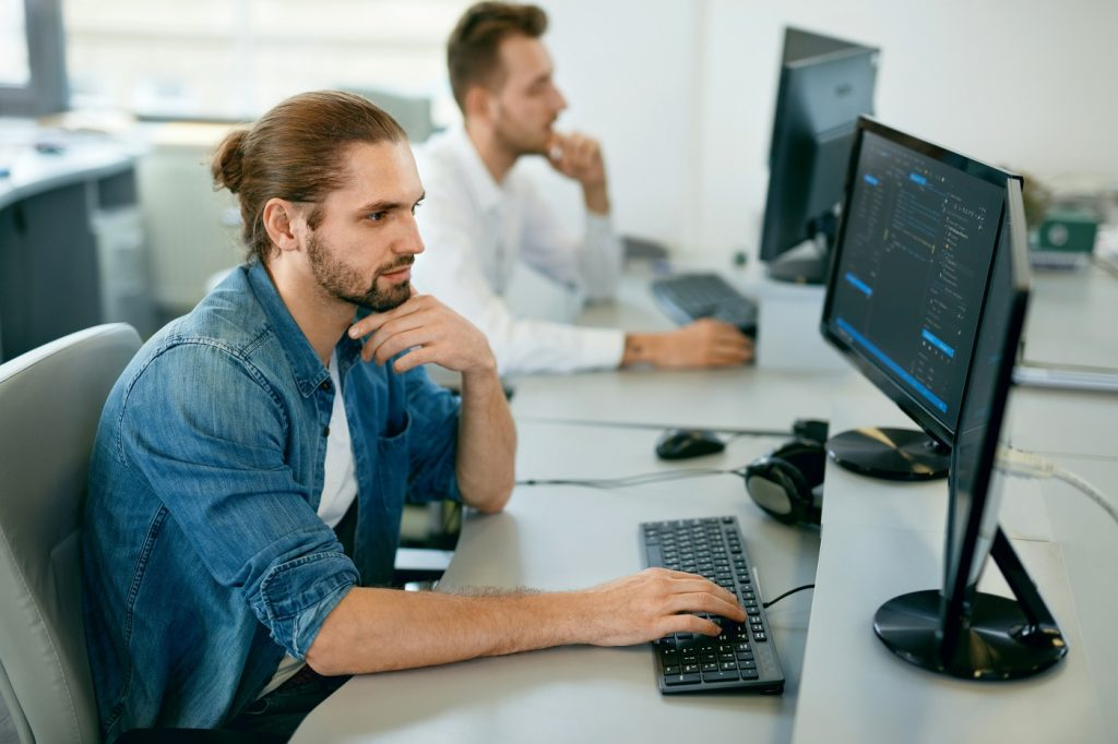 Programmers Working, Looking At Computer In IT Office.